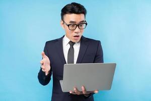Homem de negócios asiático vestindo terno olhando para o laptop e se sentindo surpreso foto