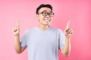 retrato de homem asiático posando em fundo rosa com muitas expressões foto