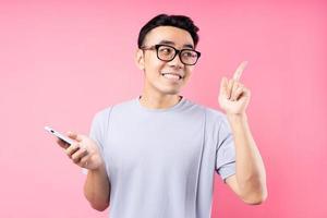 retrato de homem asiático usando smartphone em fundo rosa foto