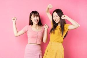 retrato de duas lindas garotas asiáticas posando em fundo rosa foto