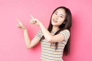 jovem mulher asiática posando em fundo rosa foto