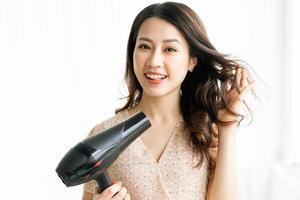 mulher sentada secando o cabelo com uma expressão feliz foto