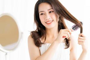 mulher sentada escovando o cabelo com uma expressão feliz foto