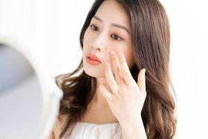 mulher asiática sentada maquiada em frente ao espelho foto