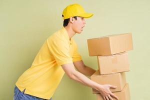 entregador asiático está segurando a caixa com ele e correndo para entregar as mercadorias foto