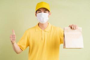 o entregador asiático mascarado estava segurando a sacola de papel e segurando o polegar foto