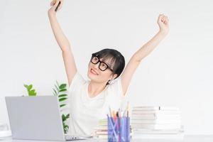 empresária asiática esticando os ombros depois de terminar o trabalho foto