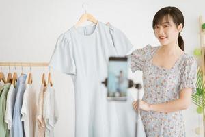 jovem asiática linda está transmitindo ao vivo para vender roupas em plataformas de redes sociais e sites de comércio eletrônico. esta será a tendência futura da indústria de comércio eletrônico foto