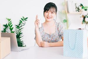 Mulher de negócios asiática está usando smartphones para transmitir ao vivo a venda de cosméticos em sites de redes sociais e sites de comércio eletrônico. foto