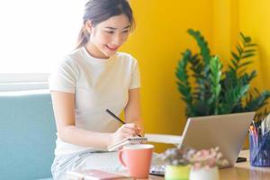 jovem mulher asiática sentada no sofá trabalhando em casa foto
