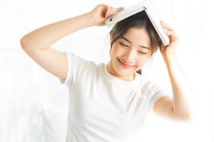 retrato de uma jovem asiática lendo um livro e tomando café foto