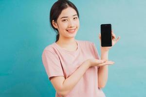 retrato de menina segurando um telefone e apontando para ele sobre fundo azul foto