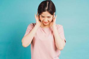 retrato de menina cobrindo as orelhas e sentindo desconforto em fundo azul foto