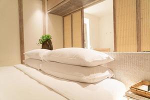 decoração de travesseiros brancos na cama em quarto de hotel resort de luxo foto
