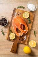 Filé de salmão cru fresco com ingredientes a bordo foto