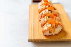 Sushi de salmão grelhado em um prato de madeira - estilo comida japonesa foto