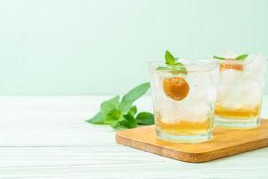 Suco de ameixa gelado com refrigerante e hortelã-pimenta na mesa de madeira - bebida refrescante foto