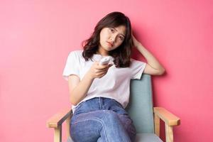 jovem asiática sentada no sofá assistindo televisão sozinha foto