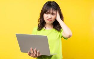 jovem asiática usando laptop em fundo amarelo foto
