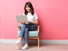 Mulher asiática sentada no sofá usando laptop com uma expressão feliz foto
