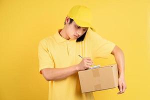 retrato de homem de entrega segurando caixa de carga e usando o telefone em fundo amarelo foto