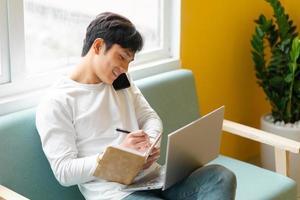 jovem asiático sentado trabalhando em casa foto