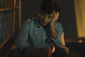 o cansado asiático bebendo sozinho na escada externa foto