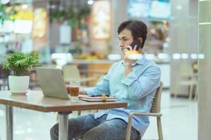 homem asiático sentado trabalhando sozinho em uma cafeteria foto