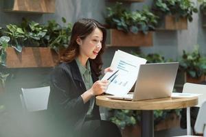 alegre jovem empresária trabalhando em uma cafeteria foto