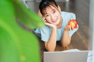jovem mulher asiática segurando uma maçã e usando seu laptop pela manhã foto