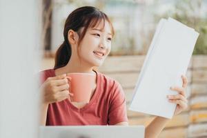 mulher asiática toma café na varanda pela manhã foto