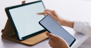 mulher asiática usando smartphone e tablet com tela em branco foto