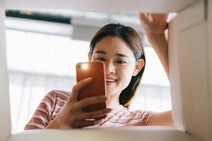 jovem asiática abre o novo pacote que foi enviado para casa foto