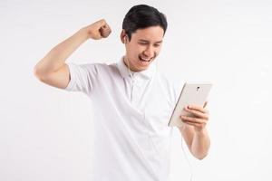 imagem de um jovem feliz em pé no fundo da parede branca isolada. olhe para o lado usando o tablet como um gesto vencedor. foto
