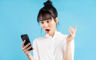 linda mulher asiática segurando o telefone sobre um fundo azul com expressão de surpresa foto