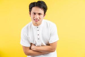 homem asiático com dor de estômago em fundo azul foto