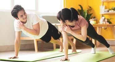 casal asiático fazendo exercícios juntos em casa foto