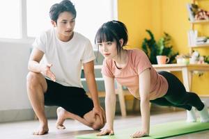 namorado asiático está instruindo a namorada para fazer exercícios em casa foto