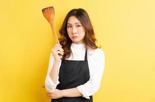 linda dona de casa segurando uma colher de arroz isolada em fundo amarelo foto