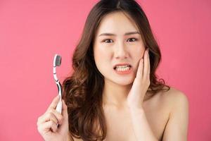 linda mulher asiática segurando escova de dentes no fundo foto