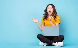 jovem sentada usando laptop com expressões e gestos no fundo foto