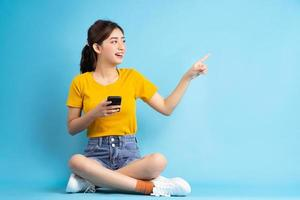 jovem mulher asiática sentada e usando o smartphone sobre fundo azul foto