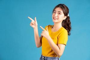 jovem mulher asiática usando o dedo para apontar no fundo azul foto