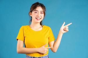 jovem asiática posando em fundo azul foto