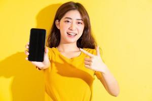 jovem asiática usando smartphone em fundo amarelo foto