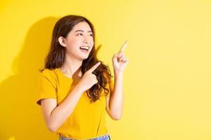 jovem asiática posando em fundo amarelo foto