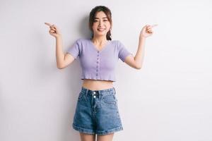 jovem asiática alegre apontando no fundo branco foto