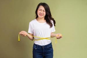 jovem asiática segurando uma fita métrica irritada com o ganho de peso foto