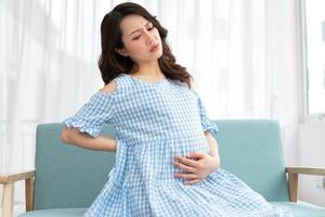 linda mulher segurando a barriga de grávida se sentindo desconfortável foto