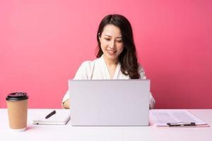 jovem empresária asiática sentada trabalhando com expressão no fundo foto
